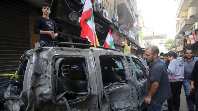 Männer stehen um ein ausgebranntes Autowrack in einer eng bebauten Strasse herum.