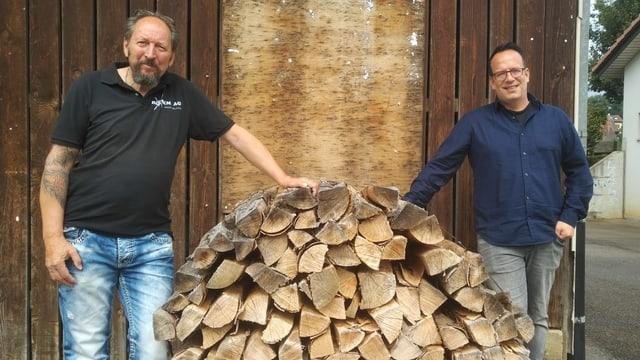 Zwei Männer stehen neben Brennholz