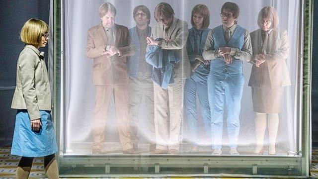 Die Schauspieler stehen auf der Bühne alle in beigen und blauen Anzügen.