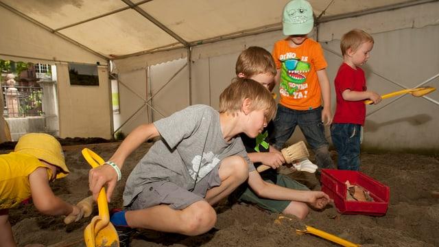 Kinder graben in einem riesigen Sandkasten Vasenstücke und Münzen aus.