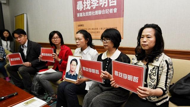 Mehrere Frauen sitzen auf einer Bank, sie haben Schilder mit chinesischer Schrift in die Höhe, die Frau in der Mitte hält ein Foto in den Händen.