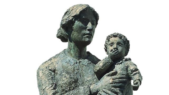 Frau hält Kind, das sich die Hand vor den Mund schlägt.