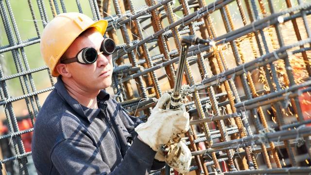 Schwesser mit Schutzbrillean Metallgerüst.