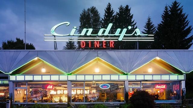 Eine Autobahnrestaurant in der Nacht, darüber steht in Neonschrift «Cindy's Diner».