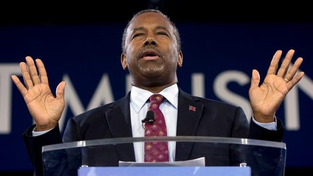 Carson mit geschlossenen Augen an einem Rednerpult, die Hände erhoben.