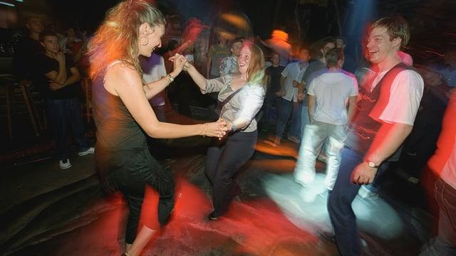 Zwei jungen Frauen tanzen auf einer Tanzfläche, ein junger Mann schaut ihnen lachend zu. Es hat farbige Lichter und im Hintergrund sieht man noch andere Menschen.