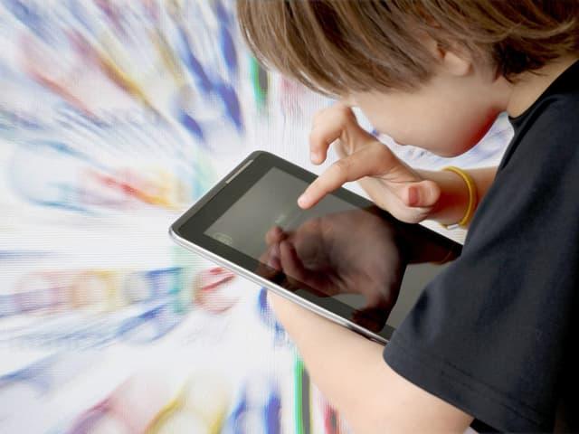 Ein Kind an einem Tablet. Im Hintergrund das Google-Logo.
