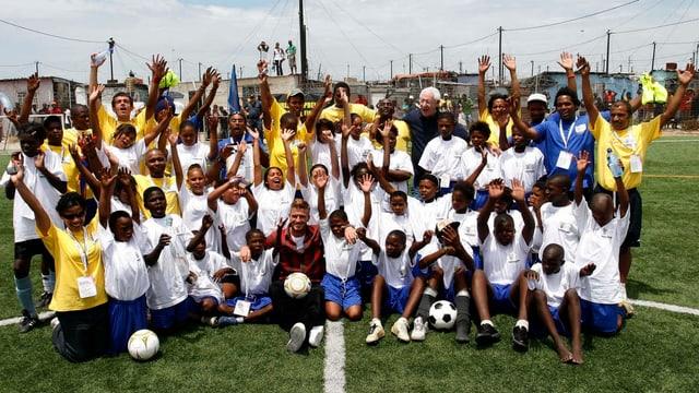 Eine Gruppe Kinder posiert mit David Beckham.