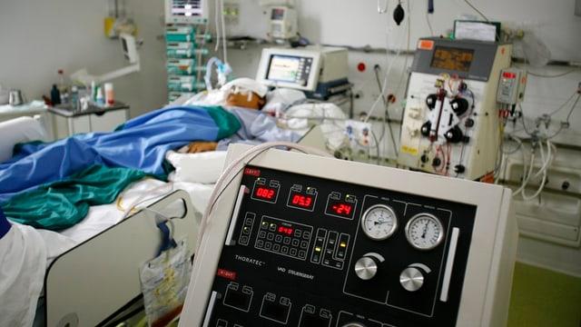 Eine Person liegt in einem Spitalzimmer, umgeben von viel medizinischem gerät. Die Person ist im Hintergrund und nicht erkenntbar, im Vordergrund sieht man ein Gerät mit verschiedenen Anzeigen.