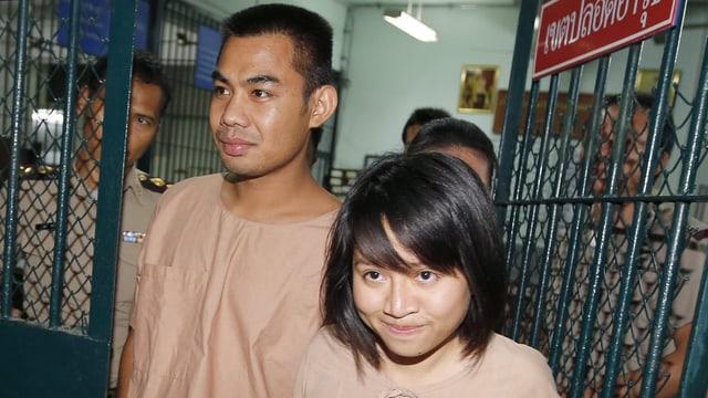 Zwei Personen in Gefängniskleidung.
