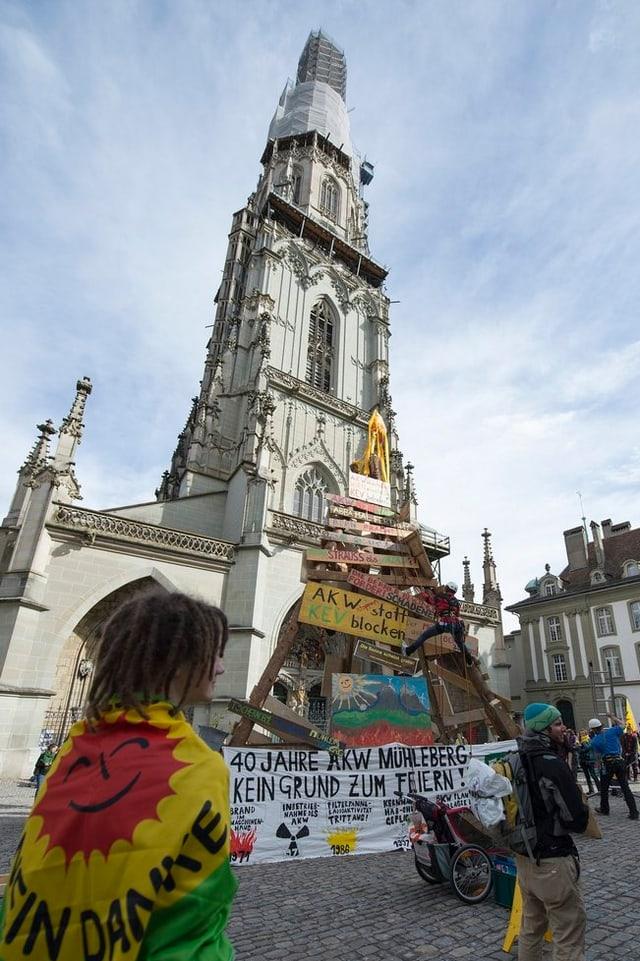 Holzturm mit Transparenten vor dem Berner Münster.