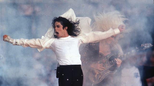 Michael Jackson auf der Bühne. Er streckt beide Hände waagrecht aus. Ein Windmaschine föhnt sein Haar gegen oben. Er singt.