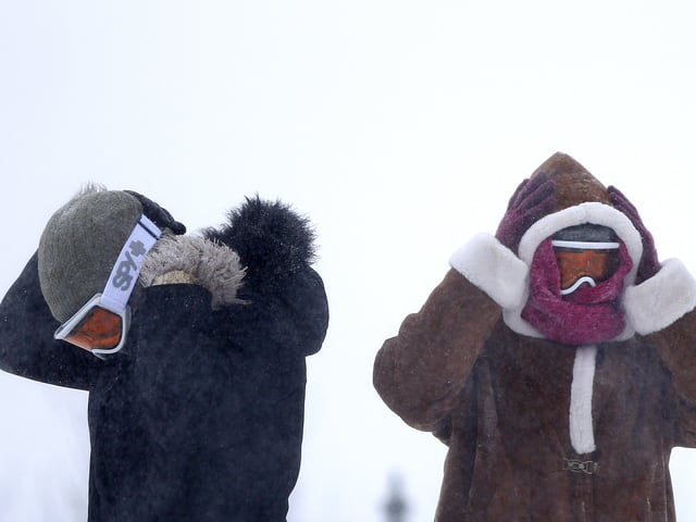 Zwei Spaziergänger im Schneesturm halten sich die Ohren unter ihren Winterkappen zu. Sie tragen zusätzlich Halstücher und Skibrillen.