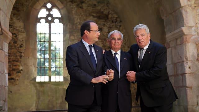 Drei Männer in Anzügen Arm in Arm in einer Kirchenruine