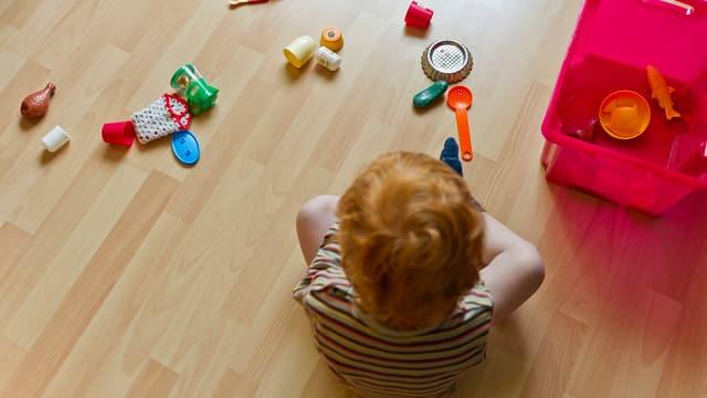 Kind sitzt vor Spielzeug auf dem Boden.
