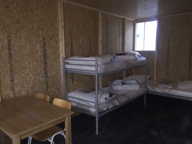 Stock-Bett und Bett in dunklem Raum mit Spanplattenwänden und einem kleinen Fenster im Hintergrund.