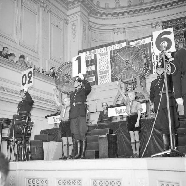 Schwarz-weiss: Drei Männer auf einer Bühne mit Nummernschildern in den Händen