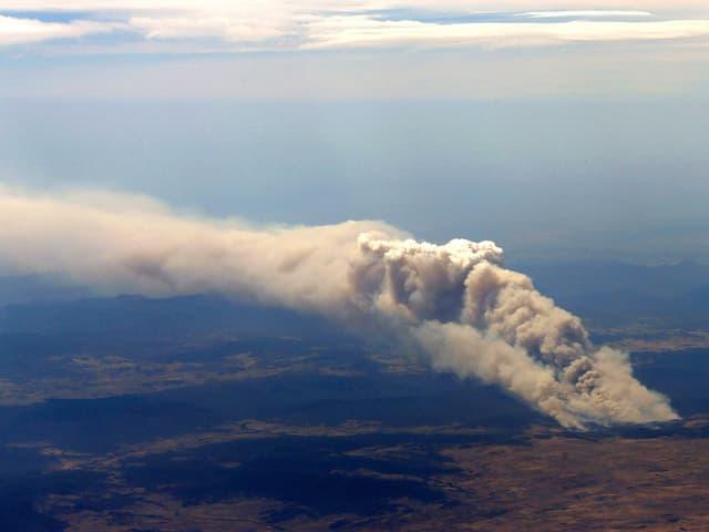 Sicht aus einem Passagierflugzeug auf eine weit in den blauen Himmel über Cooma aufsteigende Rauchsäule.