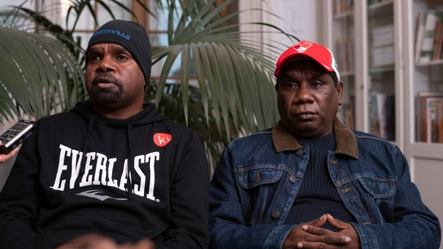 Zwei Männer starren ins Leere.