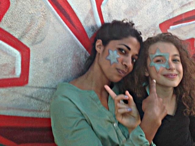 Reena und Lia in der Kaschemme vor einem Graffiti