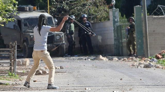Ein Mann wirft Steine mit einer Steinschleuder gegen uniformierte Sicherheitskräfte