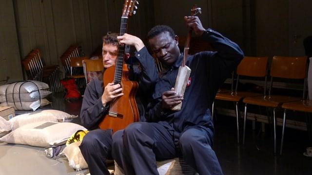 Zwei Schauspieler sitzen auf Stühlen und spielen ein Instrument.
