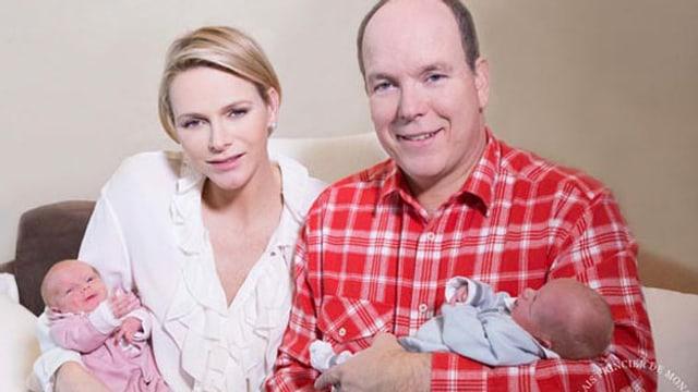 Charlène und Fürst Albert je mit einem Baby im Arm.