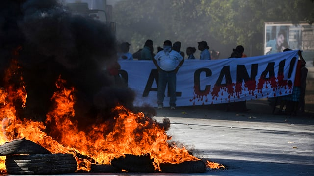 Proteste gegen den Kanal mit brennenden Pneus und Menschen, die ein Banner halten.
