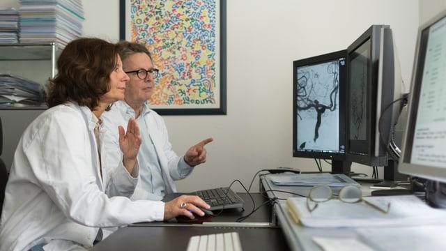 Zwei Ärzte sitzen an einem Pult vor Bildschirmen und diskutieren