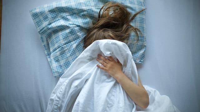 Mädchen liegt im Bett und zieht die Bettdecke über den Kopf.