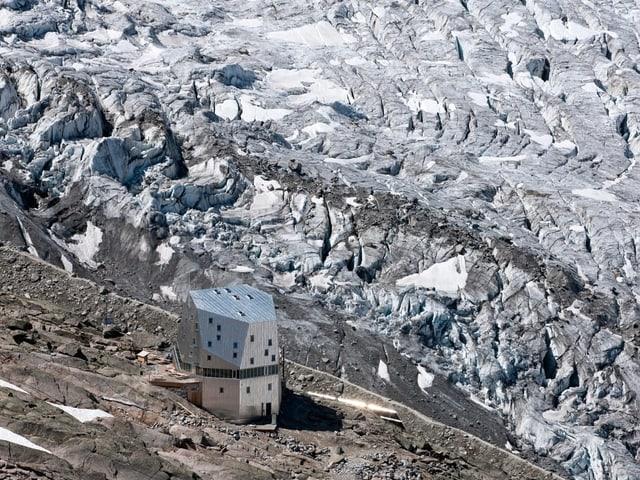 Eine SAC-Hütte vor einer Berglandschaft.