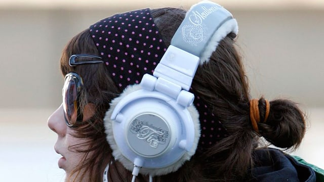 Eine junge Frau mit Sonnenbrille trägt einen grossen, silbernen Kopfhörer.
