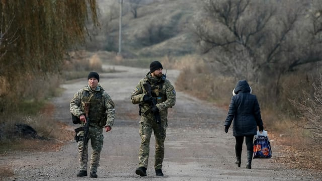 Soldaten patrrouillieren auf einer Strasse im Donbass, eine Zivilistin geht vorbei.