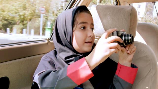 Ein Mädchen mit einem Kopftuch sitzt im Taxi und fotografiert.