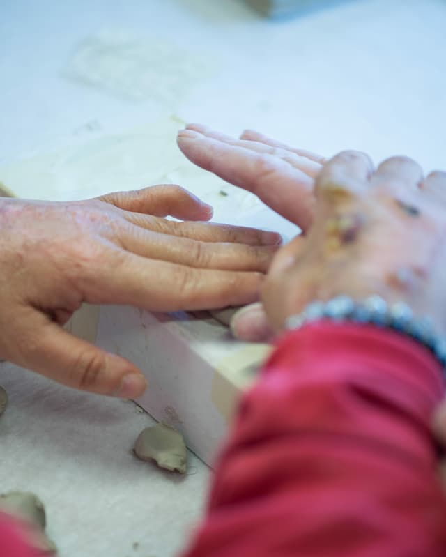 zwei Paar Hände, die Steine fühlen