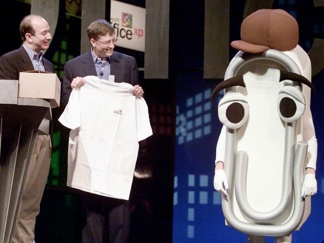 Bill Gates und eine traurige Briefklammer mit Mütze stehen auf einer Bühne, Amazon-CEO Jeff Bezos schaut zu.