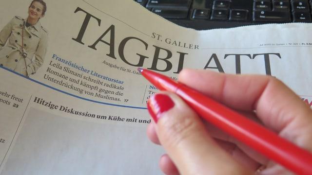 Eine Frauenhand hält einen roten Stift.