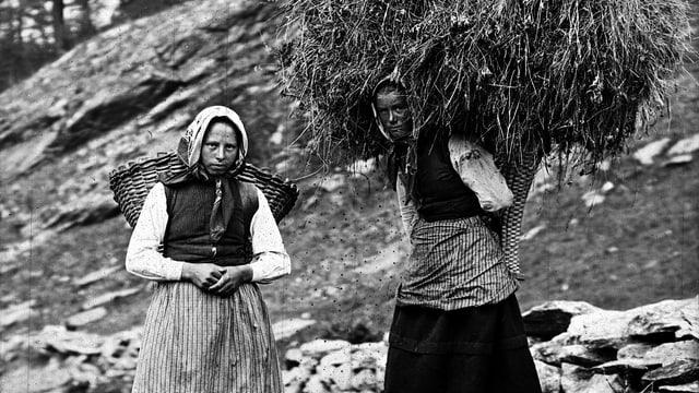 Zwei Frauen mit Kratten, einer übervoll mit Heu