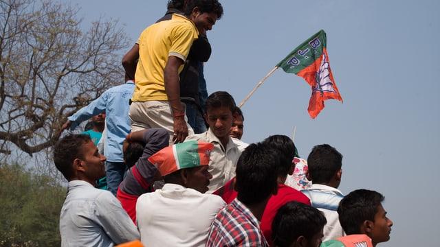 Gruppe von jungen Männern halten BJP-Fahne.