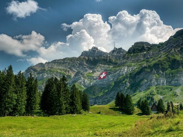 Säntis mit riesiger Schweizerfahne, dahinter Gewitterwolken