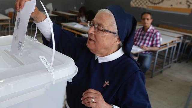 Eine Nonne wirft ihren Stimmzettel in die Urne.