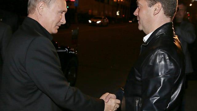 Vladimir Putin schüttelt Ministerpräsident Medwedew diee Hand.