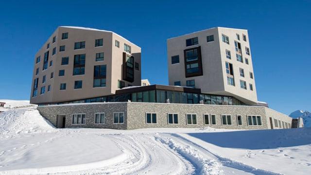Das Hotel von aussen in einer verschneiten Landschaft.