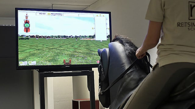 Eine Frau sitzt auf dem Reitsimulator und beobachtet dabei die Daten, die auf einem Bildschirm erscheinen.