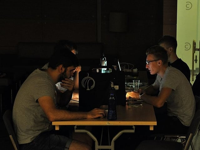 Gruppe junger Männder im Halbdunkel an einem Tisch mit verschiedenen Computern.
