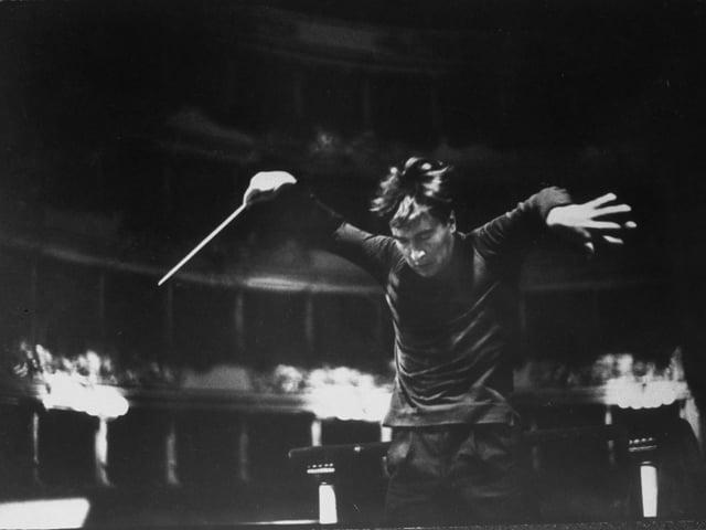 Ein Mann in schwarzem Anzug dirigiert mit wilden Gesten.