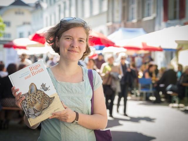 Eine junge Frau steht in einer sonnigen Altstadtgassse mit vielen leuten und hält ein Kinderbuch, auf dem der Kopf eines schlafenden Leoparden zu sehen ist.