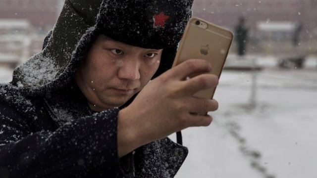 Ein Mann mit Pelzmütze macht ein Selfie.
