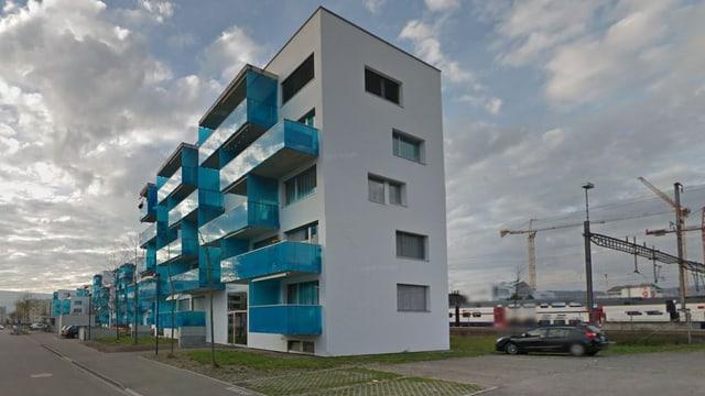 Neue Wohnbauten mit blau verkleideten Balkonen, im Hintergrund ragen Kräne in den Himmel.