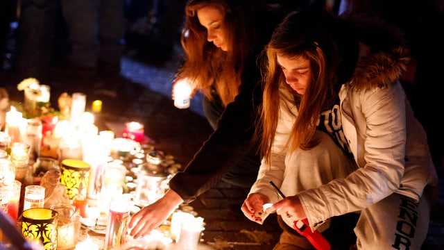 Zwei Mädchen zünden Kerzen für die Opfer des US-Amoklaufs an.